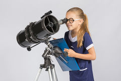 The young astronomer happy to look through the telescope recording observations Royalty Free Stock Photos