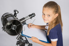 Young Astronomer writes the results of observations in the document Stock Images