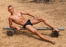Young athlet. Athletic male model on woden banch at the beach royalty free stock photos