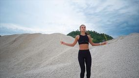 Young athlete actively jumping rope on a summer day with a stone background. A young woman in a sports suit who does exercises on a rope for endurance is engaged stock footage