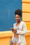Young athlete african woman with a smartphone stock photography