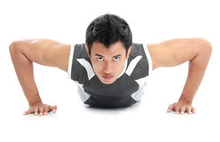 Young athlete attractive push-up attractive push-up. A close up of a man doing push ups with an intense expression on his face stock photo