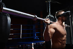Young athlete with barbell and virtual reality glasses Royalty Free Stock Photos