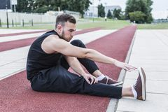 Athlete preparing for training or competitions on running track. Young athlete in black sports clothing preparing for training or for competitions on a red Stock Photos