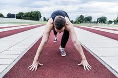 Athlete preparing for training or competitions on running track. Young athlete in black sports clothing preparing for training or for competitions on a red Stock Photography