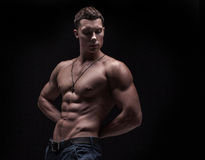 Young athlete bodybuilder man. Isolated over black background Stock Image