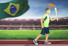 Young athlete boy with sport torch bearer running. By track at Stadium inside. Rio de Janeiro, Brazil. Brazilian flag at background. International world games Royalty Free Stock Image