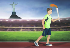 Young athlete boy with sport torch bearer running. By track at Stadium inside at Rio de Janeiro, Brazil. Corcovado Mountain with Jesus statue at background Stock Photo