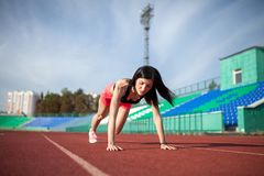 Young athlete brunette woman in shorts and tank top on stadium sporty lifestyle doing push ups on track looking aside concentrated. Young woman athlete on royalty free stock photos