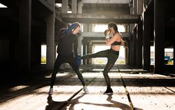Young athlete couple doing kick boxing exercise  in an old aband Royalty Free Stock Images