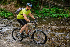 Young athlete crossing water barrier with bicycle royalty free stock image