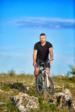 Young athlete cyclist riding mountain bike on rocky trail in the countryside. Royalty Free Stock Image