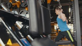 Young athlete does physical exercise in the gym. Telephoto shot Royalty Free Stock Photos