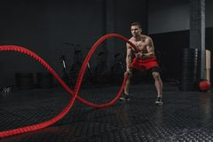 Young athlete doing battle ropes exercise at the crossfit gym royalty free stock photography