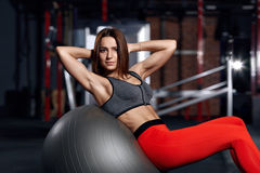 Young athlete doing exercises in the gym on fitball. Young beautiful sportswoman doing exercises in the gym on fitball. Fitness concept background Stock Photography