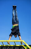 Young Athlete doing a Hand Stand On Parallel Bars In An Outdoor Gym royalty free stock image