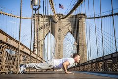 Young athlete doing pushups on Brooklyn Bridge. In New York CIty during summer sunny day royalty free stock images
