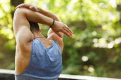 Young athlete doing stretching exercises outdoors. In summer Stock Images