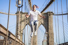 Young athlete exercising and jumping on Brooklyn Bridge. In New York CIty during summer sunny day stock photography