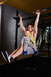 Young athlete father hangs on the horizontal bars and holds on his knees little son against brick wall. Stock Image