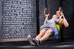 Young athlete father and little cute son exercising with gimnastic rings and smiling against brick wall in the gym. Stock Photography