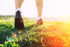 Young athlete feet running in park closeup on shoe. Male fitness athlete jogger workout in wellness concept at sunset. Runner man feet running in park closeup on royalty free stock photo