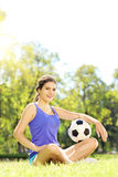 Young athlete female sitting on a green grass and holding ball i Royalty Free Stock Image