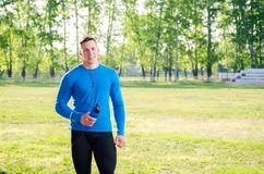 Young athlete in headphones with a bottle of water stock photo