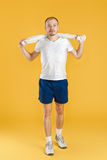 Young athlete holding towel on yellow background Royalty Free Stock Photo