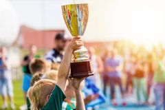 Young Athlete Holding Trophy. Youth Sport Soccer Team with Trophy. Boys Celebrating Sports Achievement. Winning Team of Sport Tournament for Kids. Children royalty free stock photo