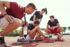 Young athlete injured to knee on the track. While being helped by his coach and his teammates Stock Photo