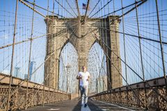 Young athlete jogging on Brooklyn Bridge. In New York CIty during summer sunny day royalty free stock photography