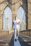 Young athlete jogging on Brooklyn Bridge. In New York CIty during summer sunny day stock photos