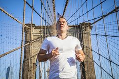 Young athlete jogging on Brooklyn Bridge. In New York CIty during summer sunny day royalty free stock photos