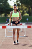 Young athlete jumping over a hurdle during training on race trac Stock Photo