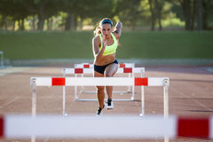 Young athlete jumping over a hurdle during training on race trac Stock Image