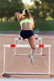 Young athlete jumping over a hurdle during training on race trac Royalty Free Stock Photos