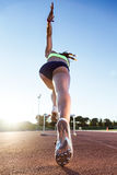 Young athlete jumping over a hurdle during training on race trac Stock Photography