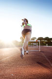 Young athlete jumping over a hurdle during training on race trac Royalty Free Stock Photo