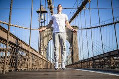 Young athlete jumping rope on Brooklyn Bridge. In New York CIty during summer sunny day stock photos