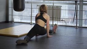 Young athlete learns to sit on the longitudinal twine in the fitness club. stock video
