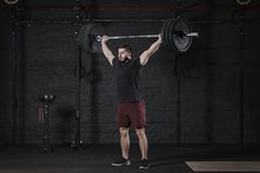 Young athlete lifting barbell overhead at the crossfit gym. Handsome man doing functional training.Practicing powerlifting. Worko royalty free stock image
