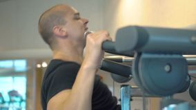 Young athlete makes a pull-ups exercise on the horizontal bar in gym stock video footage