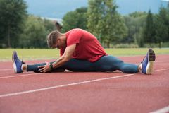 Male Runner Stretching Before Workout. Young Athlete Man Relax and Strech Ready for Run at Athletics Race Track on Stadium Stock Images