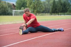 Young Fitness Man Runner Stretching Legs Before Run. Young Athlete Man Relax and Strech Ready for Run at Athletics Race Track on Stadium Stock Photography