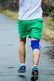 Young athlete man running down road in Park Royalty Free Stock Photography