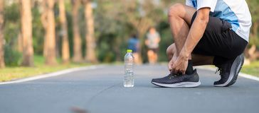 Young athlete man tying running shoes in the park outdoor. male runner ready for jogging on the road outside. asian Fitness. Walking and exercise on footpath in royalty free stock photography