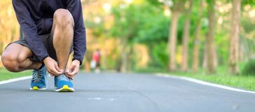 Young athlete man tying running shoes in the park outdoor, male runner ready for jogging on the road outside, asian Fitness. Walking and exercise on footpath in royalty free stock photos