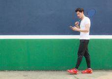 Young athlete man working on smartphone while walking in sport club. Mobile office, Freelance, Lifestyle, Internet Marketing. Telecommunication, Work Life stock photography