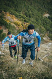 Young athlete marathon runner is ahead of his opponent on a mountain trail Stock Photo
